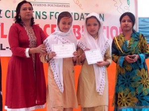 (L-R) Principal of the School with Aqsa and Nida. These girls are photographed as they receive certificates for performing brilliantly in Grade IV. They have been promoted to Grade V with flying colors.