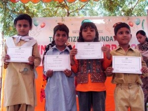 (L-R) Ramsha, Aziz-ul-Haq, Ambreen and Abid are photographed when they received certificates for performing brilliantly in their class. They have been promoted to KG.