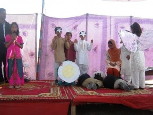 In this photograph, young primary students are presenting a tableau during the Result Day Ceremony.