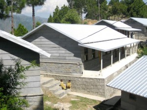 The school building surrounded by pine trees and mountains