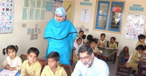 The teacher looks on as TCF CEO mingles with the students